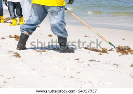 PERDIDO KEY, FL - JUNE 10: Oil spill workers collect tainted debris and dark oil patches washed ashore at Perdido Pass, AL on June 10, 2010 as oil washes ashore. - stock photo