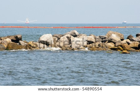 PERDIDO PASS, FL- JUNE 8: Oil boom is placed by a rock jetty in Peridido Pass, FL on June 8, 2010 as oil skimmers in the distance attempt to stop the BP oil spill from hitting the shore. - stock photo