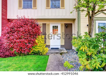 Perfect apartment entrance with white door and nice landscaping design