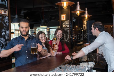 Perfect beer party. Portrait of young and handsome guy. He is standing at the bar counter and showing his beer. His female friends are standing with beer on the background and talking with each other - stock photo