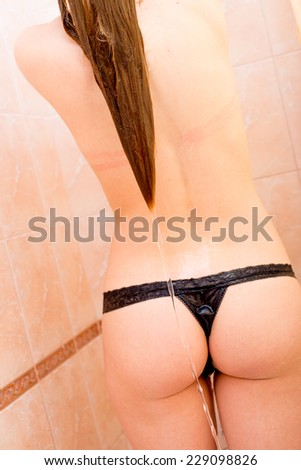 perfect buttocks: closeup picture of beautiful blond young woman having fun sensually relaxing taken shower on light copy space background - stock photo