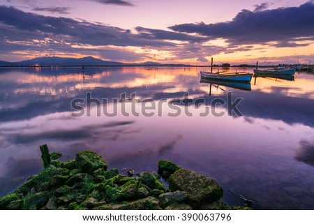 Perfect calm lagoon creates amazing reflection at sunset with a fisherman boat - specular natural image - stock photo