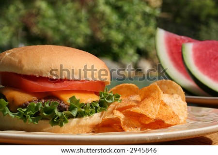 Perfect cheeseburger, with chips and watermelon, outside in summer.