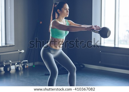 Perfect cross training. Side view of young beautiful woman with perfect body in sportswear working out with kettle bell at gym  - stock photo