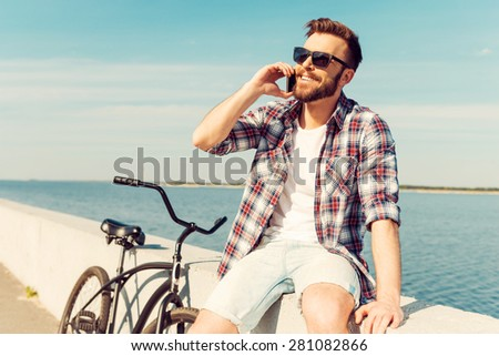 Perfect day for cycling! Cheerful young man talking on the mobile phone and smiling while sitting on parapet near his bicycle  - stock photo