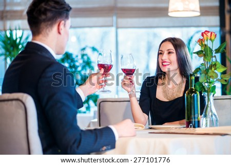 Perfect evening. Romantic dinner in the restaurant. Young couple sitting at a table at each other and smiling lovingly at the restaurant while toasting with wine. - stock photo
