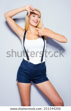 Perfect face. Beautiful young blond hair women looking at camera and gesturing finger frame while standing against grey background   - stock photo