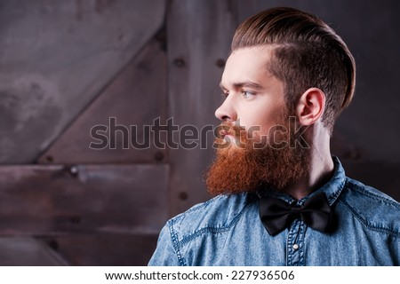 Perfect hairstyle. Profile portrait of handsome young bearded man looking away - stock photo