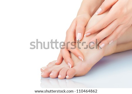 Perfect hands on female feet isolated on white background - stock photo