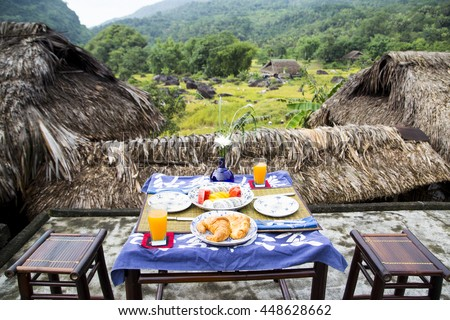 Perfect healthy breakfast on patio in summer day. Orange water, pancakes, bread, melons, mango, dragon fruit on the table against the background of mountains in Vietnam.