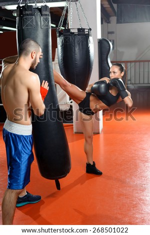 Perfect high kick. Young strong fit girl striking a punching bag with a high kick