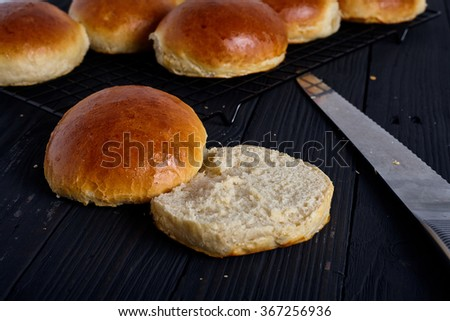 Perfect homemade bread. Burger or sandwich buns sliced on two parts  on dark wood background - stock photo