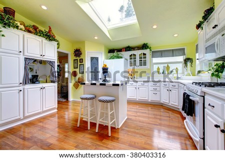 Perfect kitchen with white interior, yellow walls, and glossy hardwood floor. - stock photo