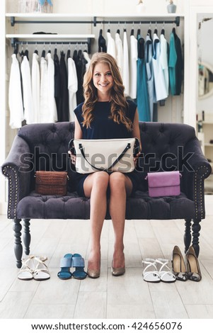 Perfect match is found! Beautiful young cheerful woman holding leather purse and looking at camera with smile while sitting on sofa at the clothing store - stock photo