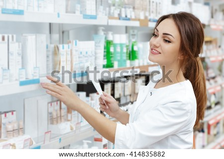Perfect medication. Shot of a young beautiful pharmacist looking for an ordered drug on a shelf at the local pharmacy. - stock photo