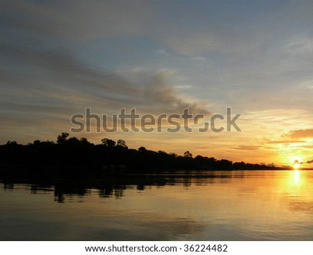 Perfect mirrored sunset on the Rio Negro in the Amazon River basin, Brazil, South America - stock photo