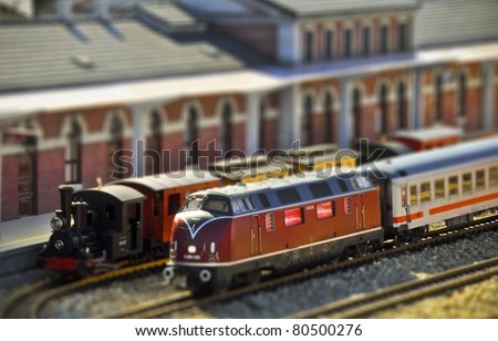 Perfect models of the older steam and newer diesel locomotives and passenger trains wait on the railway station. Tilt-shift technique. - stock photo