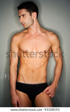 perfect naked male person in small black underwear posing in front of gray background.Ring flash used - stock photo