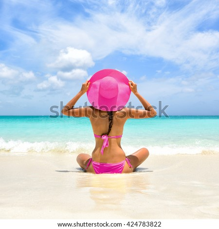 Perfect paradise summer vacation happiness carefree happy woman relaxing sitting in sand enjoying tropical beach destination. Back view of bikini girl holding pink straw hat on Caribbean holiday. - stock photo