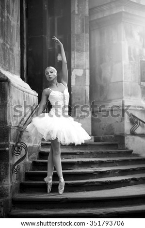 Perfect pose. Monochrome portrait of a stunning young ballet dancer posing outdoors near an old castle soft focus - stock photo