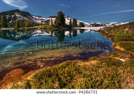 Perfect reflection in shallow mountain lake with cabin - stock photo