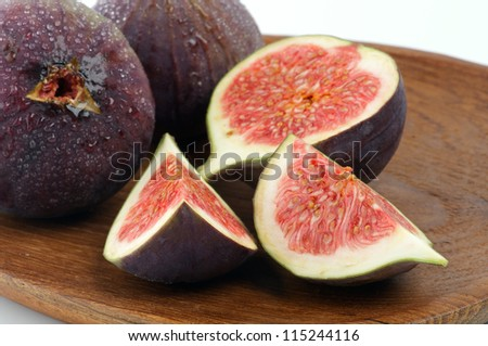 Perfect Ripe Figs Full Body and Slices with Droplets closeup on Wooden Plate