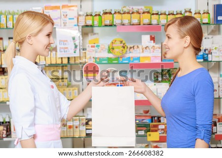 Perfect service. Young attractive pharmacist stretching out a paper bag copyscpace to the pretty smiling customer - stock photo