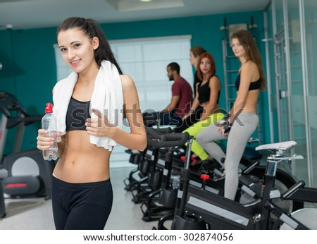 Perfect shape and ideal workout. Portrait of young and beautiful girl who is having workout in a group of exercise bikes. Perfect healthy shape. Sportsmen. - stock photo