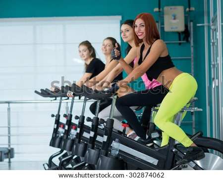 Perfect shape in a gym. Young and beautiful girl is having training on a exercise bike.. Active workout. Healthy sportsmen concept - stock photo