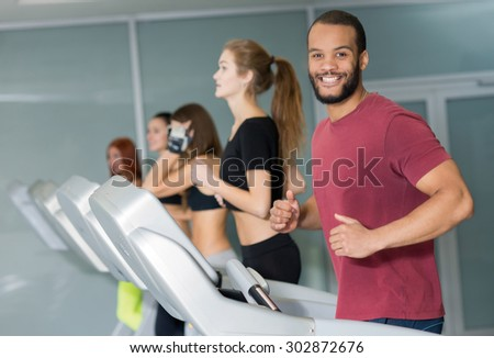 Perfect shape in a gym. Young and handsome African man is having training on a treadmill. His friends are on treadmills on the background. Active workout. Healthy sportsmen concept - stock photo