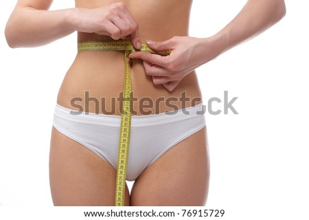 Perfect shape young woman measuring her waist with yellow tape on a wite background - stock photo