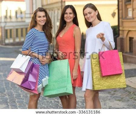 Perfect shopping. Three young pretty stylish girls are holding the shopping bags and looking forward in a good mood. Happy shopping with smiles. Road to mall and dress shops. Ideal shopping on sales