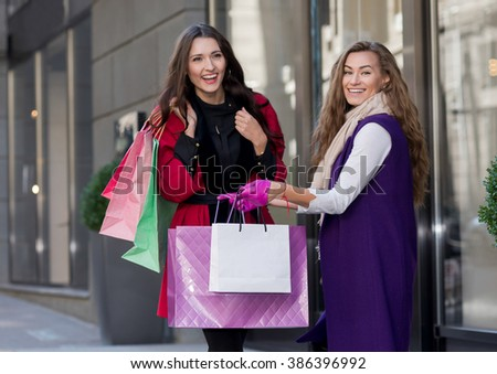 Perfect shopping. Two young pretty stylish girls are holding shopping bags and looking forward in a good mood. Happy shopping with smiles. Road to mall and dress shops. Ideal shopping. Festive sales