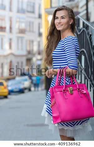 Perfect shopping with a smile. Portrait of  young pretty stylish girl holding the stylish fashionable bag and looking forward in a good mood. Ideal shopping. Mall sales and festive dress shop - stock photo