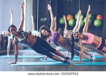 Perfect side plank. Full length of young beautiful women with perfect bodies in sportswear doing side plank and looking at camera with smile at gym - stock photo