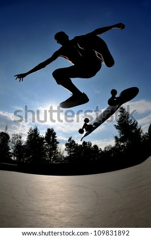 perfect silhouette of a skateboarder at a stylisch trick. - stock photo