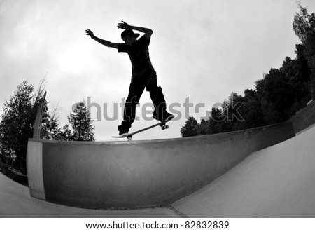 perfect silhouette of a skateboarder doing a  trick at the skate park. - stock photo