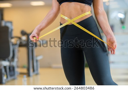 Perfect sport shape. Portrait of young and pretty athlete girl in a gym. She is metering her body and enjoys the proper sport result - stock photo