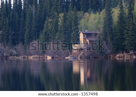 Perfect spot to spend weekend. Cabin on a lake in calm evening, - stock photo