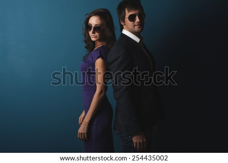 Perfect spy couple man and woman in glasses  standing back to back posing - stock photo