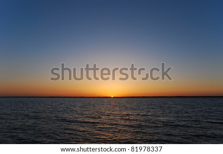 Perfect Sunset in a completely clear sky over the Solent, Isle of Wight, United Kingdom - stock photo