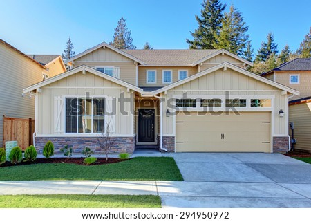 Perfect tan town house with grass, garage, and driveway. - stock photo