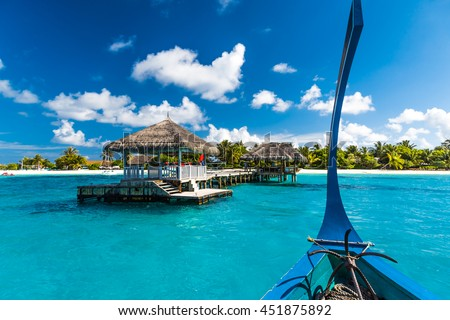 Perfect tropical island paradise beach Maldives. Long jetty and a traditional boat dhoni. - stock photo
