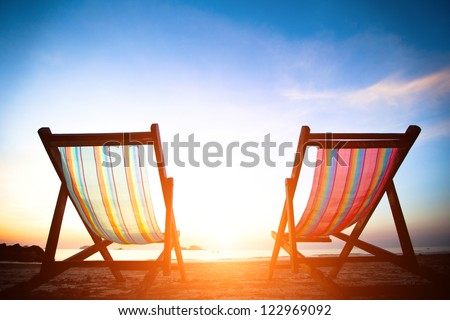 Perfect vacation concept: pair of beach loungers on the deserted coast sea at sunrise. - stock photo