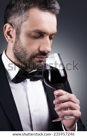 Perfect wine. Portrait of handsome mature man in formalwear smelling red wine in his glass and keeping eyes closed while standing against grey background - stock photo