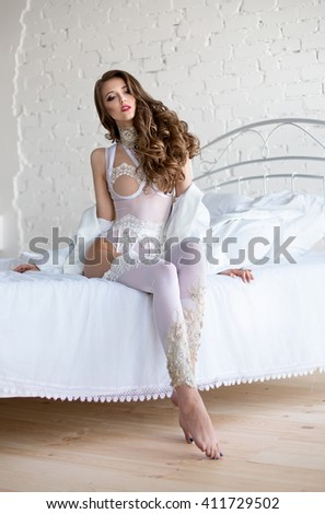 Perfect woman in a white lingerie sitting on white bed in room with brick wall