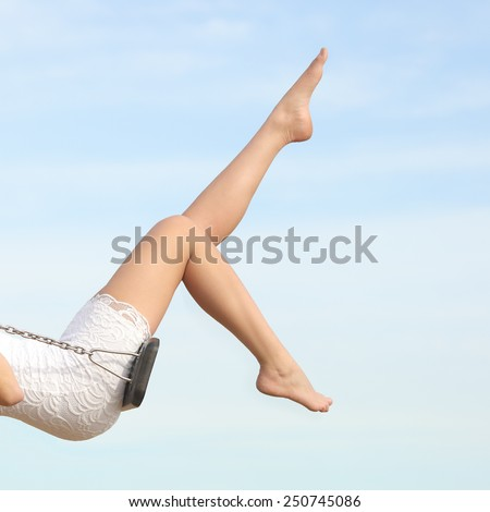 Perfect woman waxing hair removal legs swinging with the blue sky in the background - stock photo