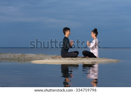 Perfect yoga. Beautiful young couple pair is balancing in lotus doing yoga. Pair yoga concept. Yoga flexibility outdoor class workout. Healthy yoga lifestyle - stock photo