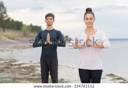 Perfect yoga. Beautiful young couple pair is doing yoga. Pair yoga concept. Yoga flexibility outdoor class workout. Healthy yoga lifestyle - stock photo