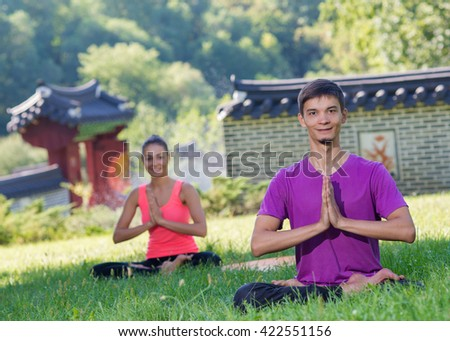 Perfect yoga. Handsome young man is balancing doing yoga. Pair yoga concept. Yoga outdoor class workout Acro-yoga. - stock photo